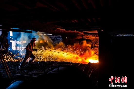 资料图:今年33岁的黄建华拿着工具前往炉口进行检查,保证铁水的正常涌出。 李南轩 摄