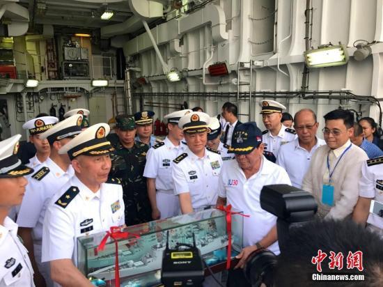 5月1日,菲律宾总统杜特尔特登上正在菲国南部城市达沃访问的中国海军长春舰参观。图为杜特尔特总统获赠一个长春舰模型。 中新社记者 张明 摄