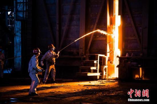 陈德茂(右)所负责的工序被称为钢水取样。在离1600多度的钢水不到两米的距离中,他不仅要仔细观察,还要使用手中的工具拨弄钢水。滚滚的热浪冲着陈德茂扑面而来,但他却依旧镇定。 李南轩 摄