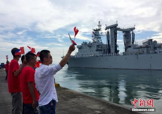 5月2日,中国海军远航访问编队圆满结束对菲律宾的友好访问,启程离开达沃港。图为当地华侨华人到码头为中国海军舰艇编队送行。 中新社记者 钟欣 摄