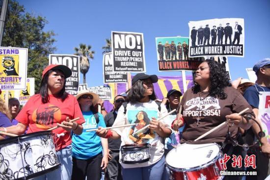 """当地时间5月1日上午,美国洛杉矶举行规模盛大的""""五一大游行"""",民众手举标语、高呼口号,表达自己的诉求。中新社记者 张朔 摄"""