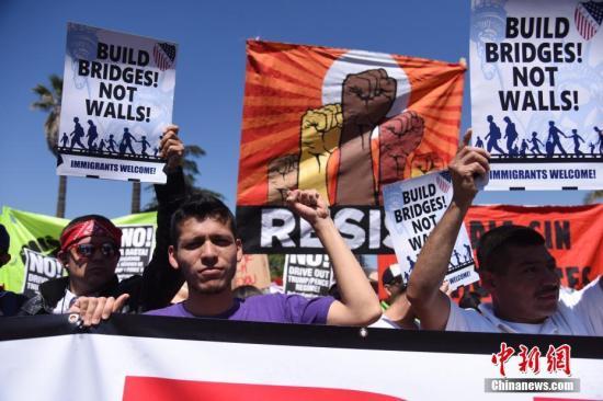"""当地时间5月1日上午,美国洛杉矶举行规模盛大的""""五一大游行"""",民众手举标语、高呼口号,表达自己的诉求。/p中新社记者 张朔 摄"""