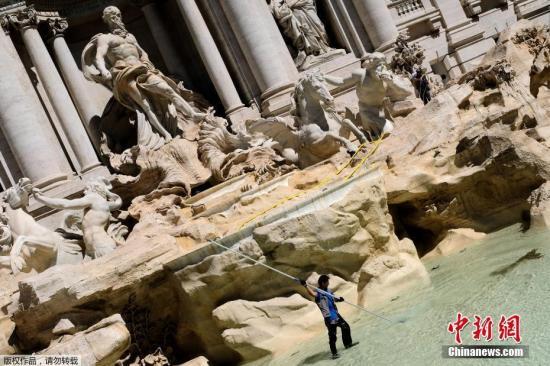 当地时间2017年5月2日,意大利罗马,一名工人在特莱维喷泉里收集硬币。每年从喷泉里收集到的硬币大约价值100万欧元。