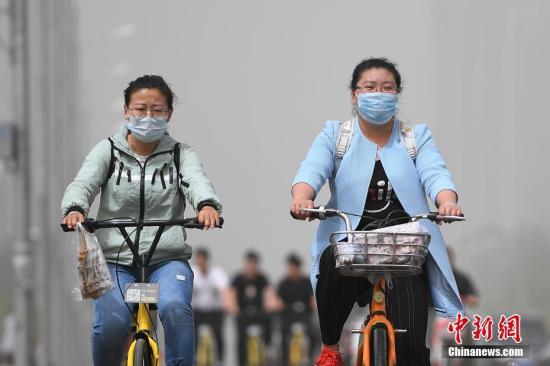 资料图:5月4日,山西太原空气质量达到严重污染级别,民众在沙尘天气中出行。武俊杰 摄