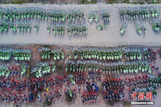 资料图:航拍一处停车场,多个颜色的共享单车停放得密密麻麻。 泱波 摄