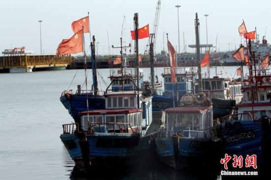 """5月5日,天津市,静谧的天津中心渔港。天津中心渔港位于滨海新区,占地约18平方公里,规划建设""""一港一城""""。海域作业港区规划泊位14个,年吞吐能力1700万吨,休闲港湾区可容纳大小游艇1000艘。定位中国北方渔业中心、水产品加工集散中心和北方游艇产业中心。图为停泊的渔船。 中新社记者 张道正 摄"""