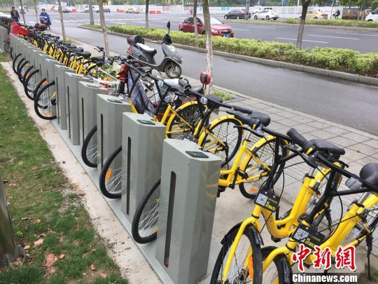 资料图 停在公共自行车停车桩上的共享单车。 孙权 摄