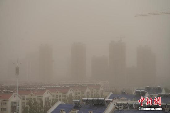 5月6日,内蒙古通辽市的城市建筑在沙尘天里朦胧不清。近日,来自内蒙古西部与蒙古国南部的沙尘席卷中国多地,位于内蒙古东部的通辽市自3日起,连续4天出现空气质量指数爆表的情况,沙尘借助大风让整个城市处在灰色之中。 中新社记者 刘文华 摄