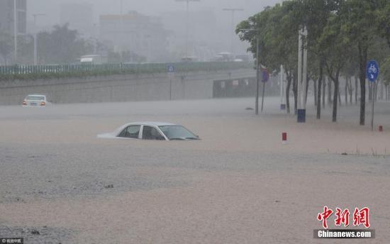 2017年5月7日中午,广州番禺区里仁洞跨线桥下道路因暴雨积水水位迅速上升,有十多部小汽车来不及通过被困水中,整条道路交通一度中断。图片来源:视觉中国