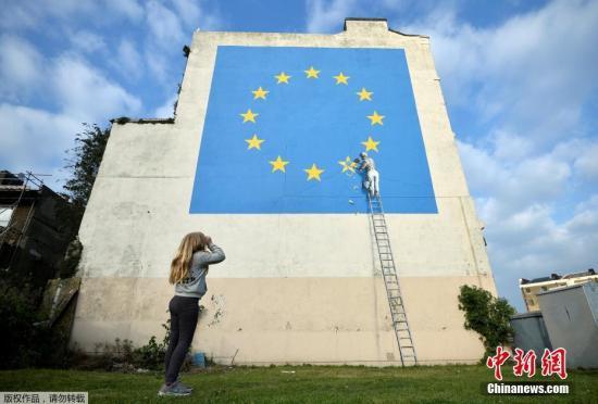 资料图:当地时间2019-02-22,英国多佛,一名街头艺术家班克西创作了一幅画,画面中一名工人正从欧盟12星旗帜上抹掉一颗星,寓意着英国将脱离欧盟。