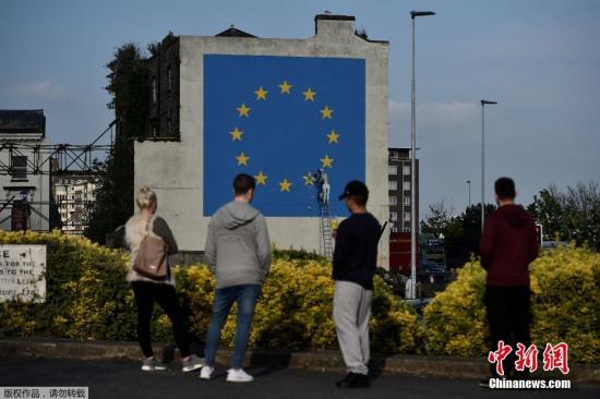 资料图:2017年5月7日,英国多佛,一名街头艺术家班克西创作了一幅画,画面中一名工人正从欧盟12星旗帜上抹掉一颗星,寓意着英国将脱离欧盟。