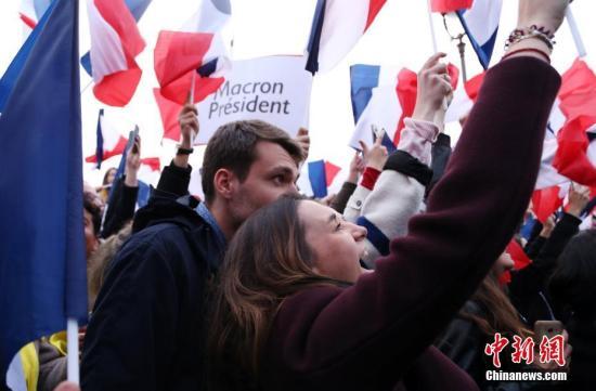 """巴黎时间5月7日晚,法国总统选举第二轮投票初步计票结果显示,中间派独立候选人、""""前进""""运动领导人埃马纽埃尔・马克龙以大幅优势击败极右翼政党""""国民阵线""""候选人马丽娜・勒庞。年仅39岁的马克龙由此成为法国史上最年轻的总统,也成为世界上最年轻的大国领导人。图为马克龙的支持者在得知马克龙当选后欢呼。 <a target='_blank' href='http://www.chinanews.com/'>中新社</a>记者 龙剑武 摄"""