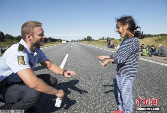 资料图:丹麦警察与难民小女孩。