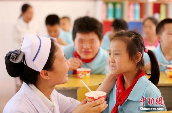 特殊教育学校,一名医护人员在喂学生吃蛋糕。 谭凯兴 摄