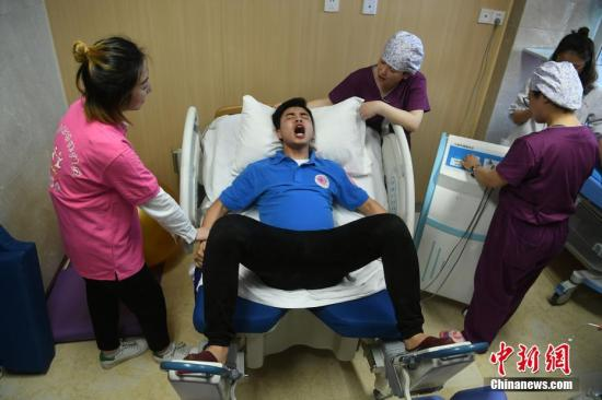 资料图:10余名已婚男士在重庆市妇幼保健院利用分娩阵痛模拟仪体验产妇分娩时的阵痛。陈超 摄