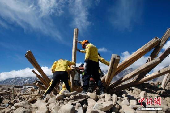 5月12日,新疆喀什地区塔什库尔干塔吉克自治县震中库孜滚村民众自建土坯房倒塌,志愿者帮助牧民转移物资。5月11日5时58分,新疆塔县发生5.5级地震,震源深度8千米。目前,地震致当地1.2万人受灾,转移安置1万人,救灾物资正在调拨当中。截至11日18时,地震共造成8人死亡、29人受伤,1.2万人受灾。倒塌房屋537户3015间,倒塌羊圈3500座,800多头(只)牲畜死亡,受损大棚150座等,地震共造成经济损失8.64亿元人民币。中新社记者 王小军 摄