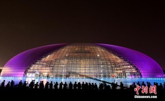 """5月12日晚间,位于北京的国家大剧院灯光璀璨,吸引市民及游客驻足拍照。5月14日至15日,""""一带一路""""国际合作高峰论坛将在北京举行。 中新社记者 侯宇 摄"""