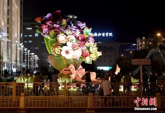 位于北京东单路口的一处花束灯光装置吸引市民及游客驻足拍照。 记者 侯宇 摄