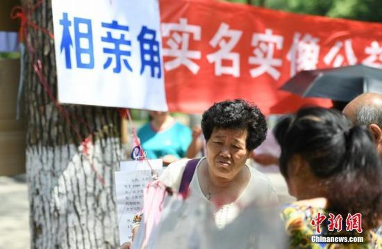 5月14日,正值母亲节,众多母亲来到长沙烈士公园内的相亲角为还未婚配的子女征婚,母亲们将子女的征婚自荐信挂在大树上,以此方式换取其他求婚者的信息。杨华峰 摄