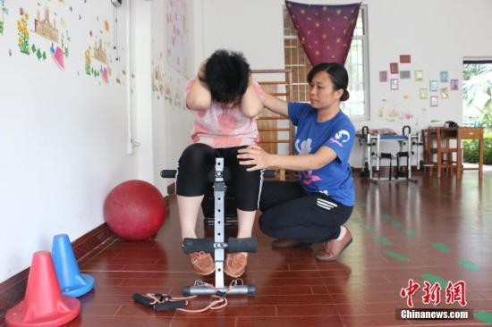 陈敬玉在帮助一名患儿做仰卧起坐训练。林馨 摄