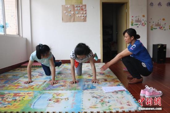 两名患儿在做康复训练,练习平衡。林馨 摄
