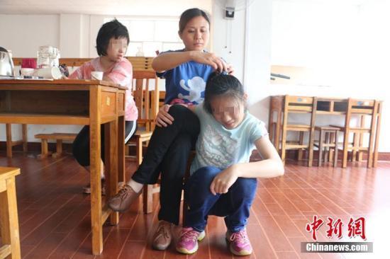 陈敬玉在给女儿梳头。林馨 摄