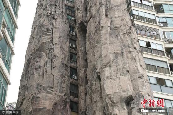 """2017年5月15日,上海长宁区一栋临街居民楼被一座假山包裹,目测这座假山高达14层有余。据了解,这座假山是楼房造好后加上去的,被假山包裹的楼房外面还挂着空调室外机,部分窗户外面还晾晒有衣服。有网友调侃:""""这才是真正的山景房"""",但也有人分析,被假山包围的房屋采光肯定不好。 左冬辰 摄 图片来源:视觉中国"""