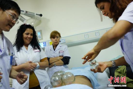 葡萄牙中医中心的医护人员在江西中医药大学附属医院医生的指导下进行拔火罐操作。 王昊阳 摄