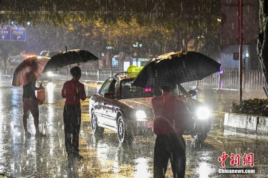 5月15日晚,广州市民冒雨在路边等待出租车。当晚,广东遭受新一轮强降雨,155个站点检测到时段降雨量超100毫米,广州市区、从化区等多地启动了高级别应急响应。 中新社记者 陈骥旻 摄