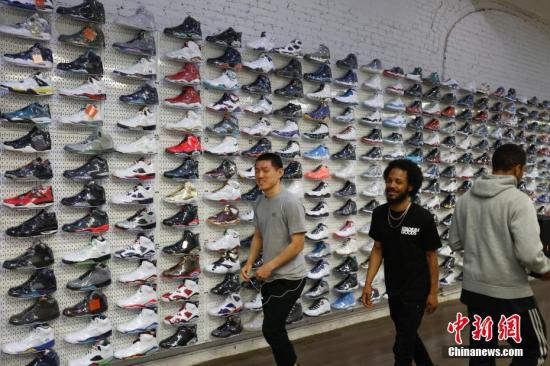 当地时间5月16日,马克菲特的店铺内正在忙碌的店员。马克菲特的潮鞋店名为StadiumGoods,位于纽约曼哈顿SOHO商业区,该店运动鞋和街头服饰齐全同时面向收藏者服务。马克菲特去年8月将店铺入驻淘宝网天猫国际后,目前通过互联网面向中国消费者的销售额已达数百万美元,他们每天通过天猫国际向中国发货数百双。 <a target='_blank' href='http://www.chinanews.com/'>中新社</a>记者 廖攀 摄