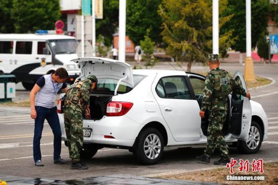 中国边防战士在中哈霍尔果斯国际边境合作中心两国连接通道检查车辆。中新社记者 富田 摄