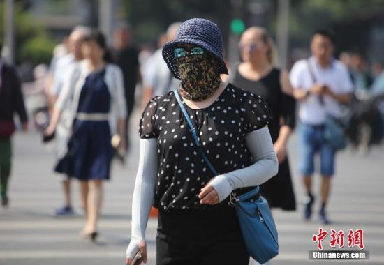 资料图:北京街头的民众防晒出行。中新社记者 杨可佳 摄