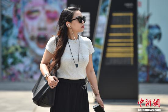 """5月17日,北京开启了高温干热的""""炙烤""""模式。图为北京三里屯街头穿夏装出行的市民。 <a target='_blank' href='http://www.chinanews.com/' >中新网</a>记者 金硕 摄"""