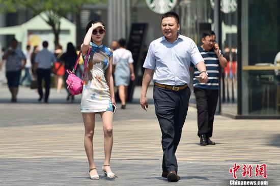 """5月17日,北京开启了高温干热的""""炙烤""""模式,气象部门预计,5月17日至19日,北京平原大部分地区日最高气温将达35℃以上,这也意味着北京或迎来2017年首个高温日。图为北京三里屯街头市民穿夏装出行。 中新网记者 金硕 摄"""