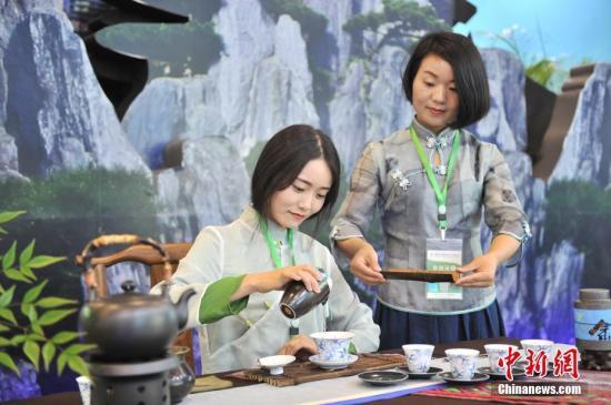 """5月18日,两名茶艺师正在展示""""功夫泡茶""""。当天,首届中国国际茶叶博览会在浙江杭州国际博览中心拉开帷幕。此次展会吸引了48个国家和地区的参展商、20个茶叶主产省份的茶企代表以及1700余家国内外专业客商报名参展。<a target='_blank' href='http://www-chinanews-com.qihaochi.com/'>中新社</a>记者 张茵 摄"""