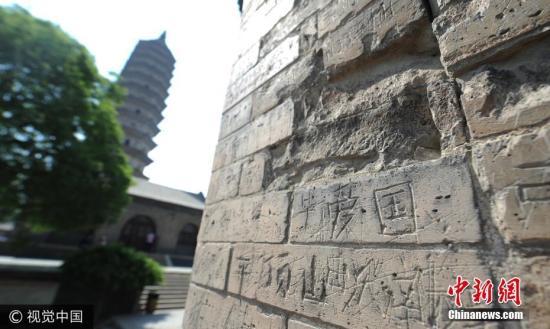 2017年5月18日,山西太原,地标性建筑永祚寺双塔,塔壁惨遭刻字留名。图片来源:视觉中国