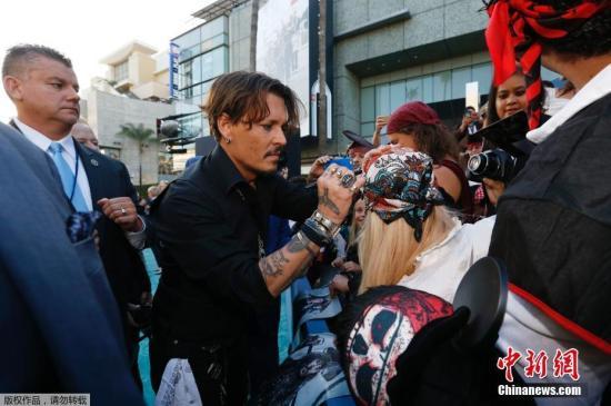 """当地时间5月18日,电影《加勒比海盗5:死无对证》在洛杉矶举行首映式,剧中主要角色都悉数登场。""""杰克船长""""约翰尼・德普的到场更是让粉丝激动不已,一名粉丝甚至要求德普在自己的头上签名。"""