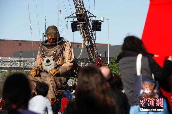 """当地时间5月19日,法国Royal de Luxe巨型木偶出现在加拿大蒙特利尔街头,通过与民众零距离的街头行进表演庆祝蒙特利尔建城375周年。巨型木偶在蒙特利尔的表演将持续三天。图为身高近十米的""""潜水员""""木偶结束第一天的表演。 中新社记者 余瑞冬 摄"""