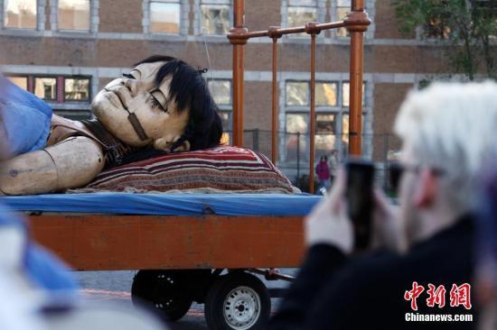 """当地时间5月19日,法国Royal de Luxe巨型木偶出现在加拿大蒙特利尔街头,通过与民众零距离的街头行进表演庆祝蒙特利尔建城375周年。巨型木偶在蒙特利尔的表演将持续三天。图为身高7.5米的""""小女孩""""木偶结束第一天的表演后躺下""""休息""""。 中新社记者 余瑞冬 摄"""