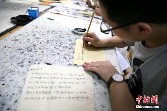 5月21日,在陕西咸阳师范学院于右任书法学院内,数十名大学生手执毛笔用小楷书写着家书。自2016年以来,该院256名学生每逢母亲节、父亲节便用小楷书写家书一封,如今学院要求学生每月写一封。该院开展此项活动,旨在开展孝文化感恩教育,还原古代文人部分日常生活形式,为学生营造一个高雅的学习氛围。 张远 摄