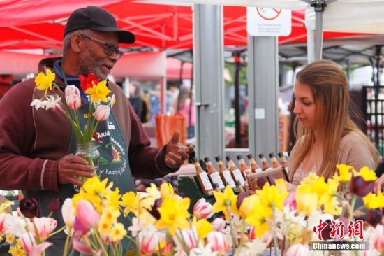 """当地时间5月21日,年轻女顾客向花农购买郁金香。久负盛名、一年一度的加拿大郁金香节于5月中下旬在渥太华举行。至少200万株各色郁金香绽放在城市各个角落,吸引世界各地大批游客前来领略这座""""郁金香之都""""的风采。中新社记者 余瑞冬 摄"""