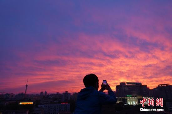 资料图:北京雨后现壮美火烧云,民众拍摄美景。 中新社记者 苏丹 摄