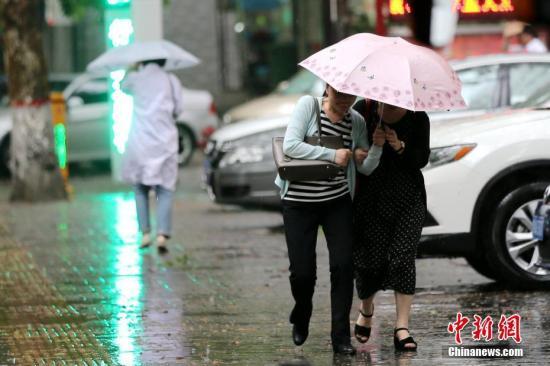 西安民众雨中出行。 中新社记者 张远 摄