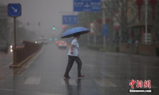 5月22日,民众在雨中出行。当日北京迎来全市范围内降雨天气,预计局部地区将达到大雨级别,气温也随之骤降。<a target='_blank' href='http://www.chinanews.com/'>中新社</a>记者 杨可佳 摄