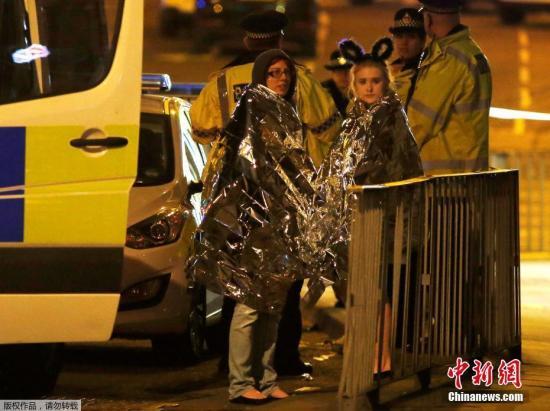 该体育场可以容纳2万人,目前不清楚具体有多少人现场观看当晚的演唱会。事件发生之后,警方部署了超过400名武装警察。图为在体育场附近,两名歌迷身上包裹着保温毯取暖。