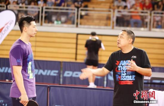 图为主教练刘国梁(右)在给男队主力马龙指导。中新社记者 沈晨 摄