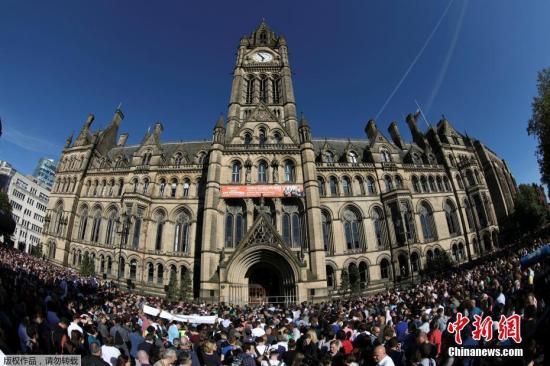 """当地时间5月23日下午,数千名民众在曼彻斯特市中心举行集会,谴责前一晚在曼彻斯特体育馆发生的恐怖袭击行为。数千人汇聚在曼彻斯特市政厅前的阿尔伯特广场。曼彻斯特市政厅降半旗,向恐怖袭击事件中的遇难者致哀。参加集会的民众,有些人手捧鲜花向遇难者表示哀悼,有些人高举写着""""我爱曼彻斯特""""的标语牌。"""