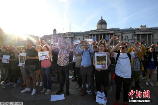 当地时间5月23日,英国伦敦特拉法加广场,民众向天空比心,悼念曼彻斯特爆炸遇难者。
