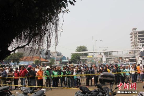5月24日晚,印尼首都雅加达东区一公交车站发生两起爆炸,已造成至少5人死亡、10人受伤。图为25日上午,大批媒体记者在现场报道,民众围观。中新社记者 林永传 摄