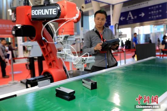 资料图:制造业博览会上,一参展商正在操作机器人手臂。 中新社记者 王舒 摄